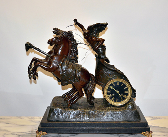 Lot 114: Fairly large bronze wash spelter mantle clock; young gladiator racing with horses on a chariot. H53xW53xD30cm.