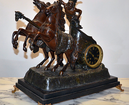 Lot 114_1: Fairly large bronze wash spelter mantle clock; young gladiator racing with horses on a chariot. H53xW53xD30cm.