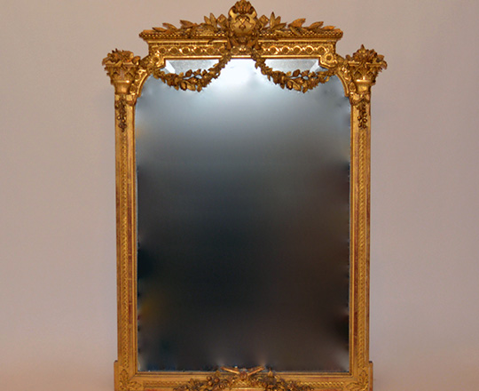 Lot 125: 19th cent Louis XVI gold leaf bevelled mirror with finely ornated top.(small acc.) H129 x W90cm.
