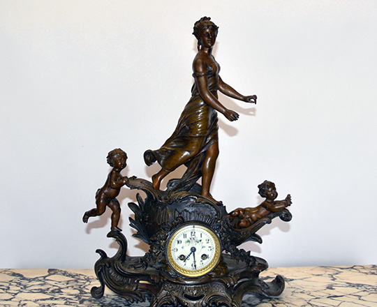 Lot 126: Turn c bronze wash spelter mantel clock with puttis sailing with young woman. H52xW36cm.