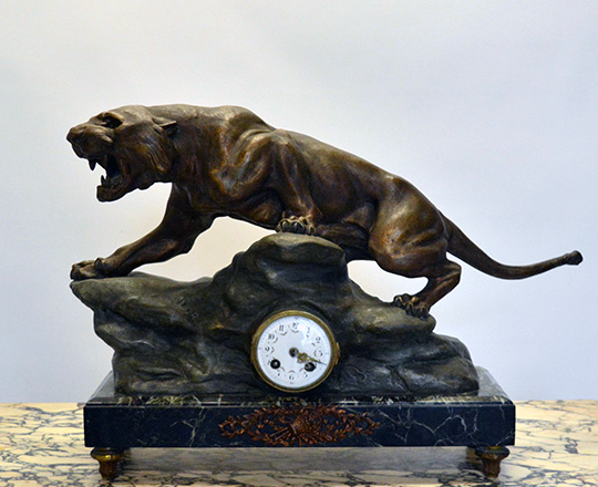 Lot 128: Early cent bronze wash spelter mantel clock; lioness signed 'Cartier'. H43xW63cm.