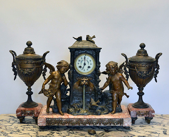 Lot 159: 19th c bronze wash spelter clock garniture of two puttis by fountain (of youth?) H41cm and lidded vases H39cm