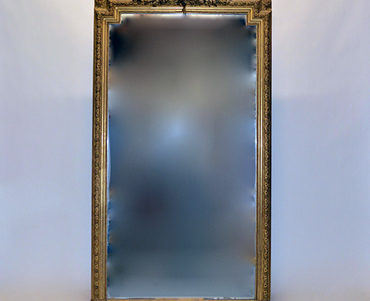 Lot 568: Tall 19th cent Louis XVI gold leaf mirror with rich ornated top. H199 x W110cm. (scratches on mirror).