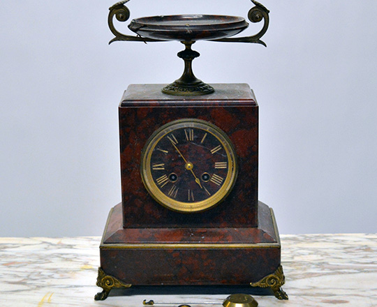 Lot 584: 19th c Nap.lll red marble mantle clock topped with a dish and a pair of cassolettes with repair on dishes.