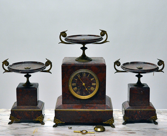 Lot 584_2: 19th c Nap.lll red marble mantle clock topped with a dish and a pair of cassolettes with repair on dishes.