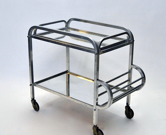 Lot 596: Art Deco aluminium bar cart on wheels with removable tray. (acc. on bottom mirror) H76xW72xD40cm.